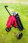 picture of golf bag  - a wheeled golf bag full of golf clubs of a vibrant golf course - JPG