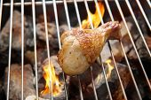 pic of flame-grilled  - Chicken legs grilling over flames on a barbecue - JPG