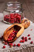 image of peppercorns  - Red peppercorns in wooden scoop on burlap - JPG