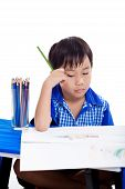 picture of boring  - Asian boy thinking and boring emotion at the table with images paper and colour pencils - JPG
