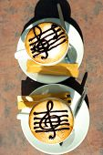 image of treble clef  - Cups of cappuccino with treble clef on foam on table in cafe - JPG