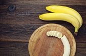 image of bunch bananas  - Bunch of bananas and a sliced on a dark wooden table top view - JPG