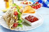 pic of tacos  - Tasty taco with nachos chips and tomato dip on table close up - JPG