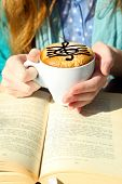 stock photo of treble clef  - Hands holding cup of cappuccino with treble clef on foam - JPG