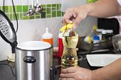 foto of chef cap  - Chef open cap of vegetable oil bottle before cooking - JPG