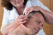 Woman Acupuncturist Prepares To Tap Needle Around Ears Of Man poster