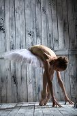 image of ballerina  - Ballerina dressed in white tutu makes lean forward. The picture in the studio wooden background.
