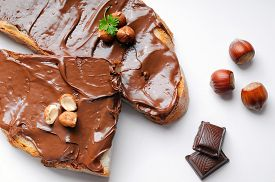 stock photo of hazelnut  - Two slices of bread with chocolate cream and hazelnuts white isolated top view - JPG