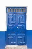Постер, плакат: A blue antique door with white wall