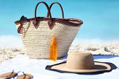 Womens beach accessories on sand for summer vacation concept. Straw tote bag, sun hat and sunscreen poster