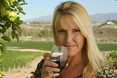 Beautiful smiling woman at a country winery tasting wine on a summer day.
