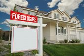 Blank Foreclosure Sign and House with dramatic sky background. Ready for your own message.