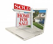 Sold Home for Sale Sign & New Home on Laptop isolated on a white Background.
