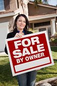 Happy Attractive Hispanic Woman Holding For Sale By Owner Real Estate Sign In Front of House.