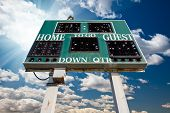 High School Scoreboard Over Blue Sky with Clouds and Sun Rays.