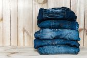 fashionable clothes. pile of jeans on a wooden background poster