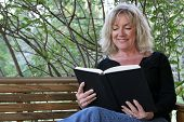 A beautiful woman enjoying a good book on her porch swing.