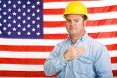Patriotic american worker with his hand over his heart in front of the US flag.  Photographed in front of flag, not composite image.