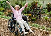 Beautiful senior lady in wheelchair is overjoyed because she has triumphed over her health problems.