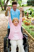 Physical therapist helping a disabled senior woman to regain mobility in her upper limbs.