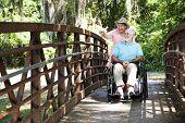 Senior mujer empujando a su marido con discapacidad a través del parque en su silla de ruedas.