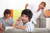 Handsome young man making a call with his friends doing the same in the background