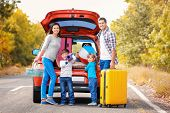 Happy family with luggage near car. Traveling concept poster