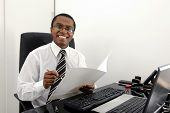 Happy bookkeeper reading documents at desk