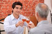Young man and senior chinking wine glasses