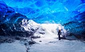Traveler in ice cave, man standing underground inside of a glacier, climate specific, Vatnajokull Na poster