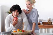 a couple in the kitchen, the man is eating an apple