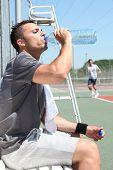 Man drinking water on tennis court sideline