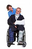 Photo of an injured man in a wheelchair with a female nurse pushing him, isolated on a white backgro