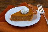 A Slice Of Pumpkin Pie On Wood Table