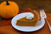 A Slice Of Pumpkin Pie And Pumpkin On Wood Table