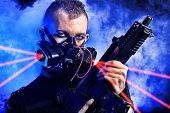 pic of skinheads  - Shot of a conceptual man in a respirator holding a gun - JPG