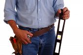 Carpenter wearing a toolbelt holding a long level isolated over white