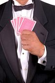 Man in Tuxedo Holding a Hand of Poker Cards