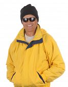 Smiling man in yellow anorak, watch cap and sunglasses isolated over white. Torso only in vertical f