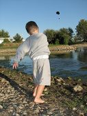 Little Boy Throwing A Rock In The Pond