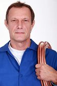 Plumber with coiled copper pipe over shoulder