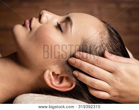 poster of Masseur doing massage the head and hair for an woman in spa salon