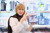 Blonde girl wearing scarf holds blender in supermarket; shallow depth of field
