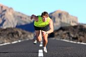 Sprinter. Man running on road at high speed in beautiful exotic mountain landscape. Male athlete run