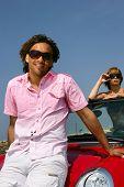 chico mostrando cerca roadster con chica guapa