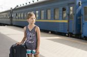 Little Sweet Girl With A Big Suitcase On A Deserted Railway Platform. Girl Pulling A Large Suitcase  poster