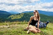 Attractive Happy Woman Hiker Hiking Mountain Trail, Resting On Grassy Hill With Trekking Sticks And  poster