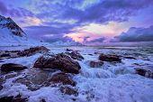Waves of Norwegian sea on rocky coast in fjord on sunset. Skagsanden beach, Lofoten islands, Norway poster