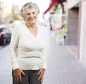 pretty senior woman smiling against a street background