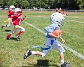 Unidentifiable kids playing flag American football poster